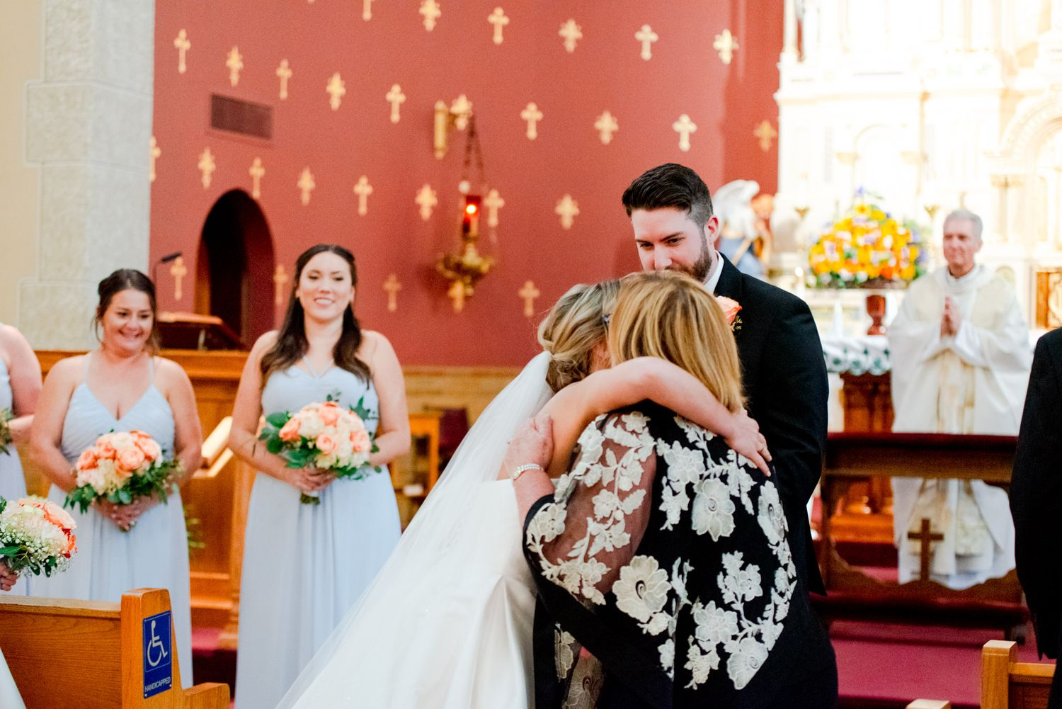 mother and bride hugging before handing bride off to groom