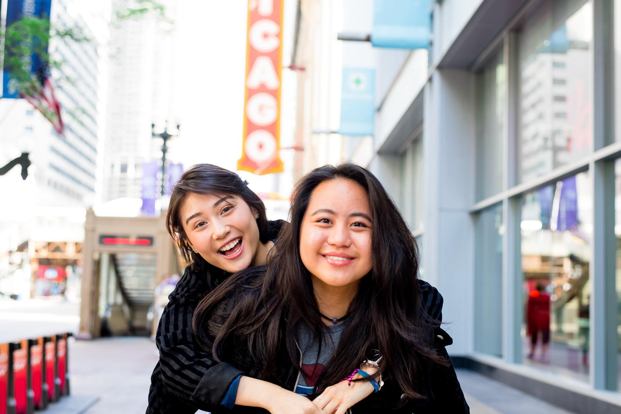 two senior girls in front of the Chicago Theater sign for Chicago senior pictures with piggyback ride