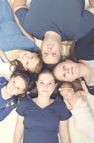 Family laying on floor looking up at camera with heads together