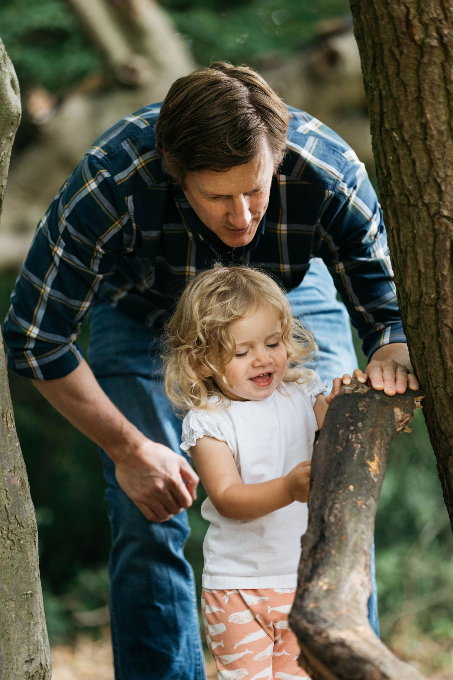 dad and daughter playing in forest