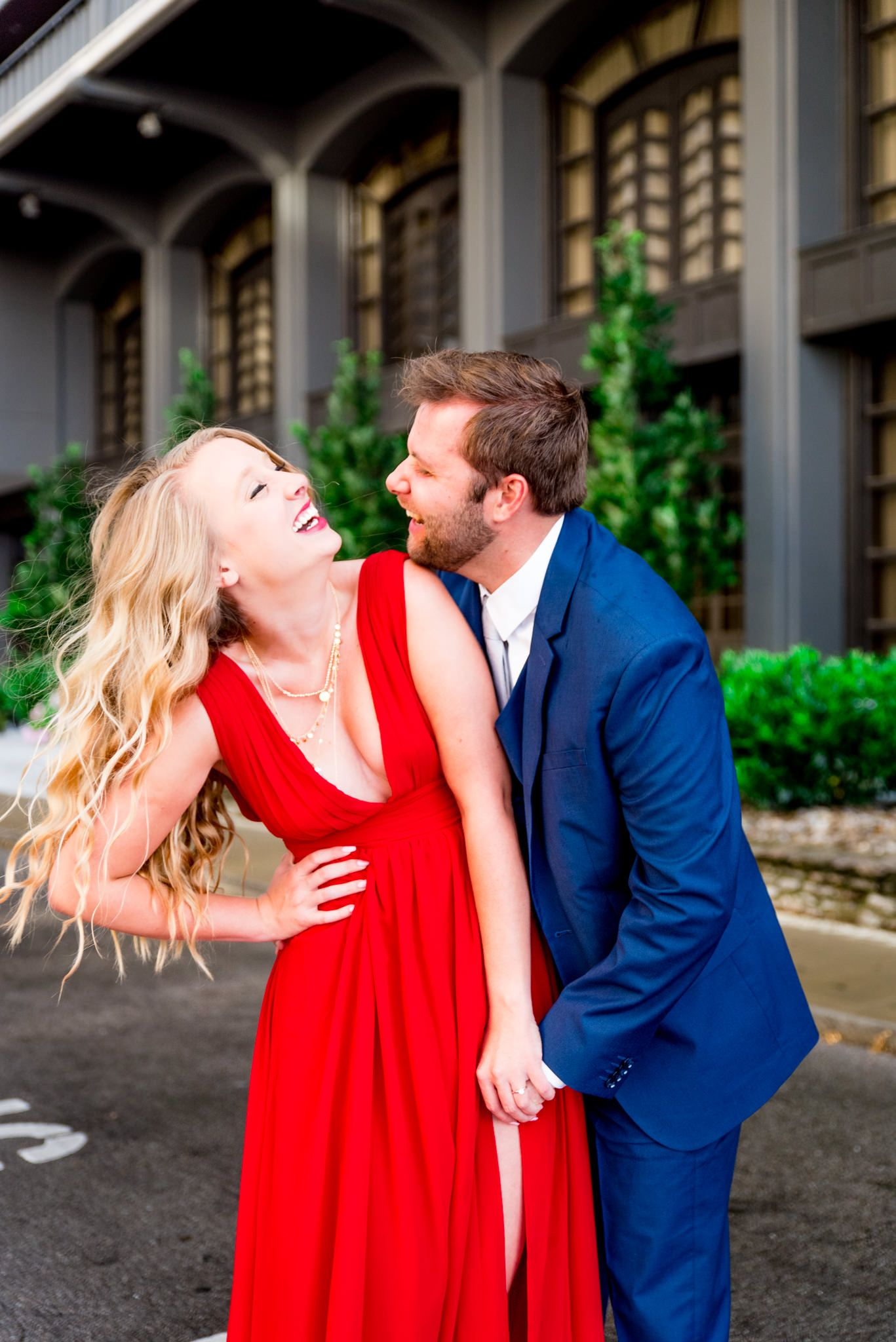 blonde woman in red dress laughing with fiance in navy blue suit tries to kiss her