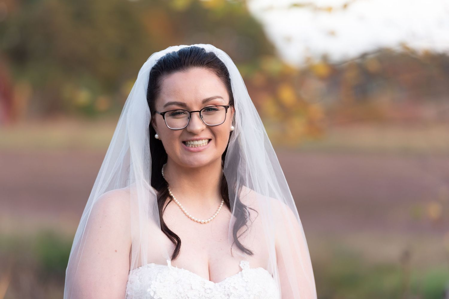 Leah Ramuglia Bride with veil smiles by cranberry bogs and fall foliage at Rosebrook Event Center in Wareham, MA