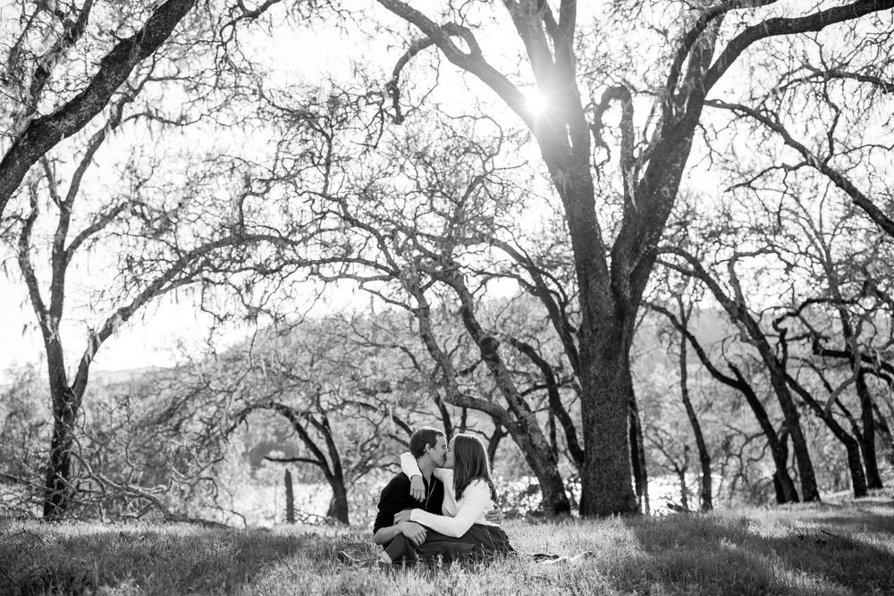 rebecca skidgel photography lake hennessey engagement shoot couple cuddling in the grass