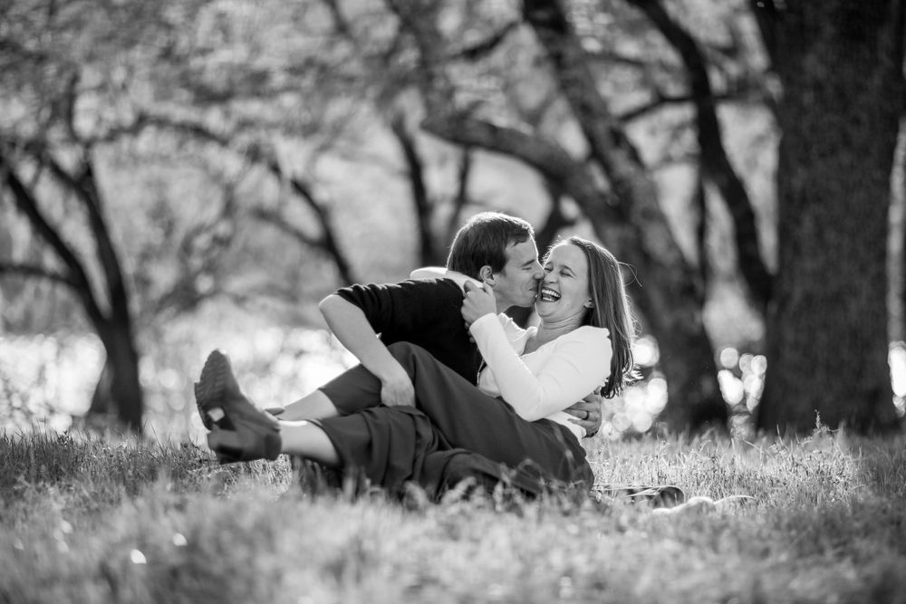 rebecca skidgel photography lake hennessey engagement shoot couple cuddling in the grass laughing
