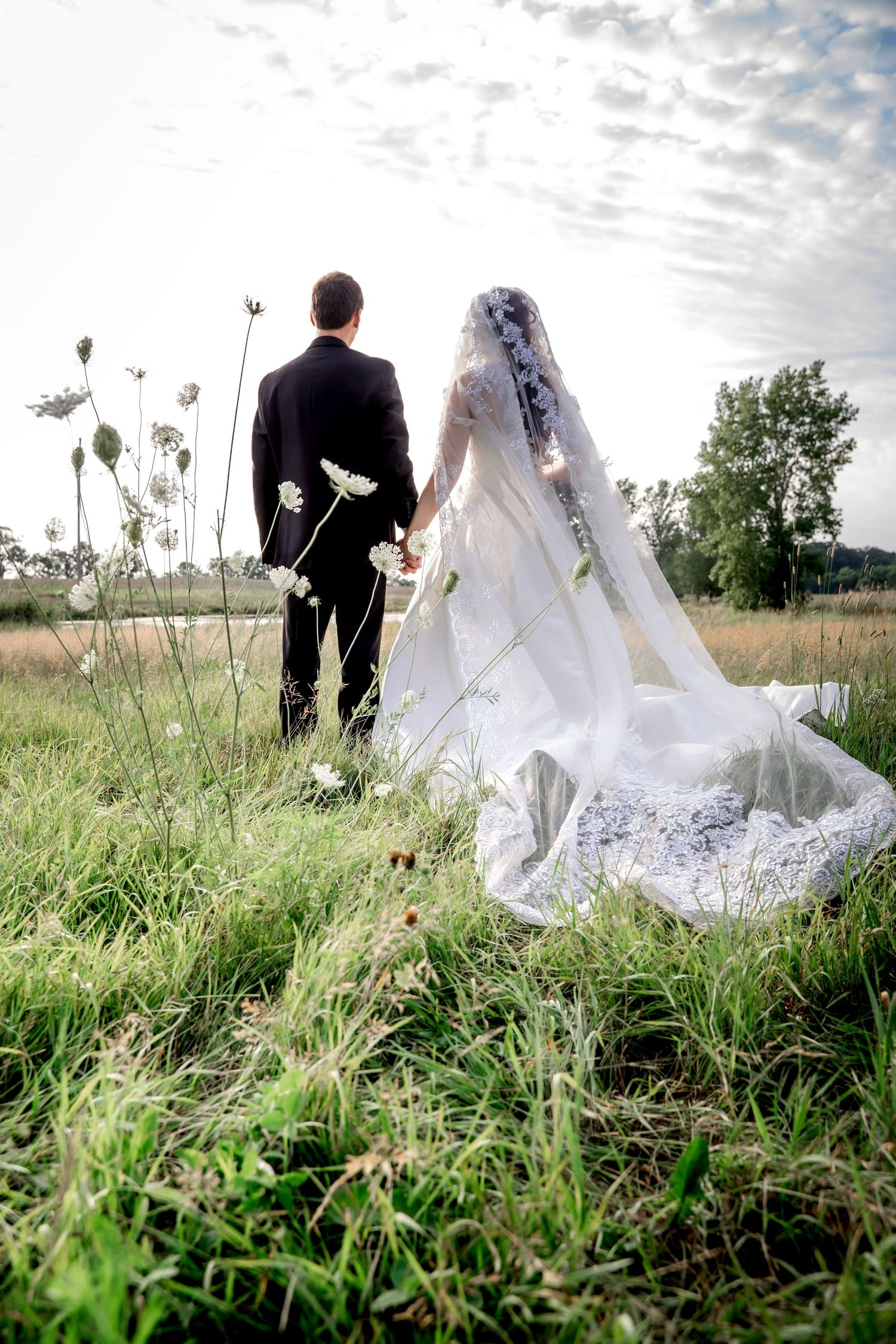 Bride and groom in a field with Queen Anne's Lace by Kalamazoo Wedding Photographer Almost Fantasy