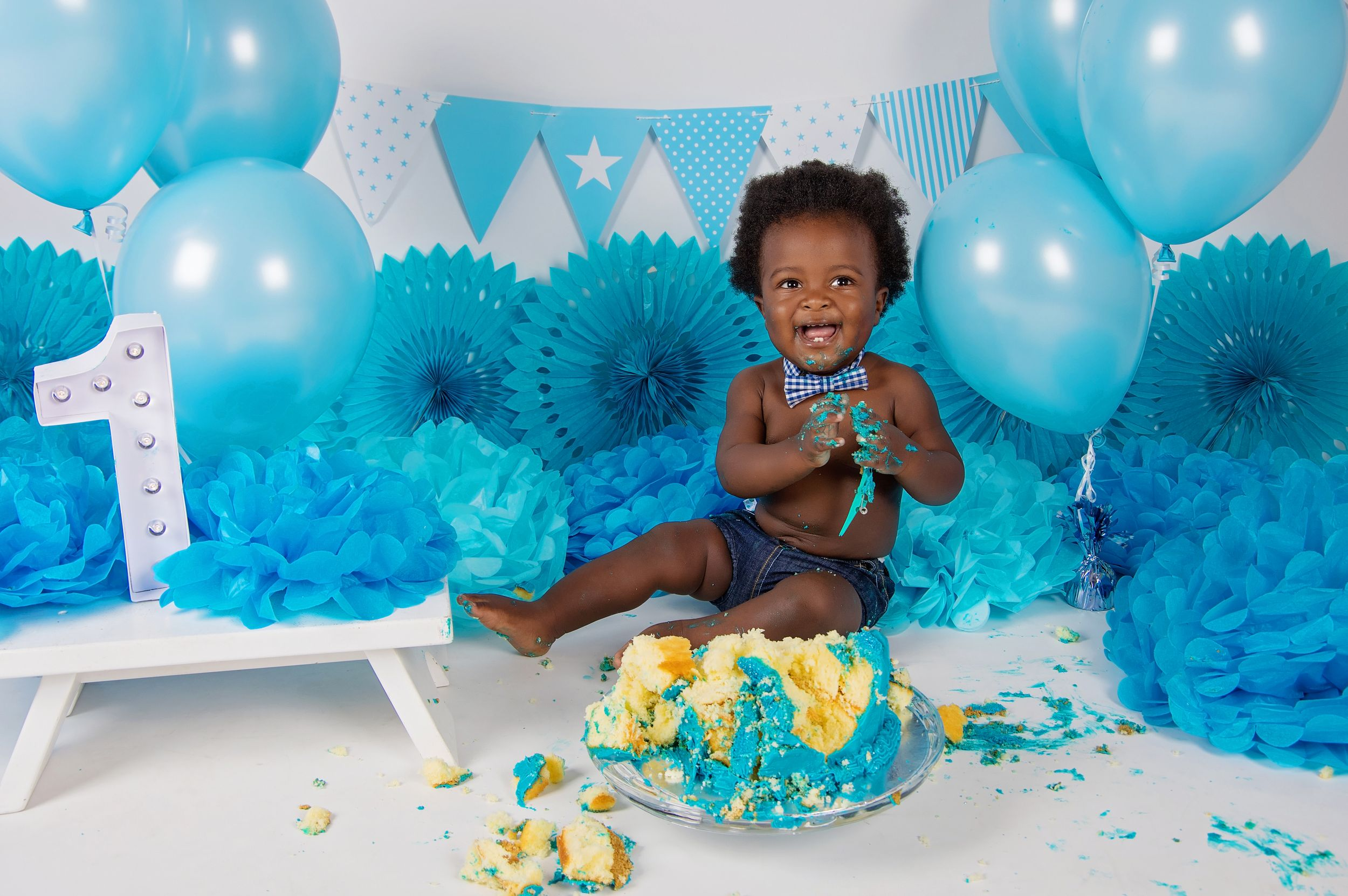 baby boy surrounded by blue decorations and balloons eating cake and laughing