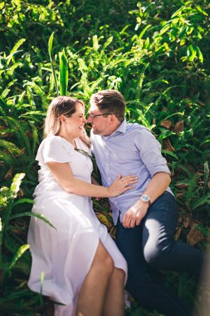 Engagement photo of couple in ferns laughing