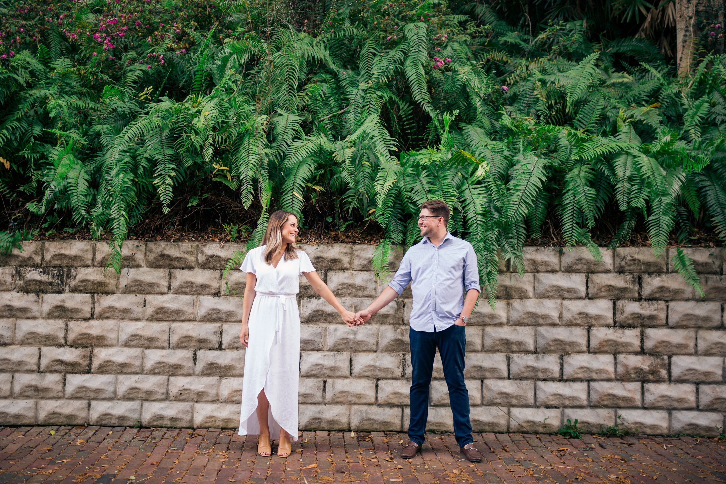 Engagement photo of couple holding hands with ferns and bricks in st pete