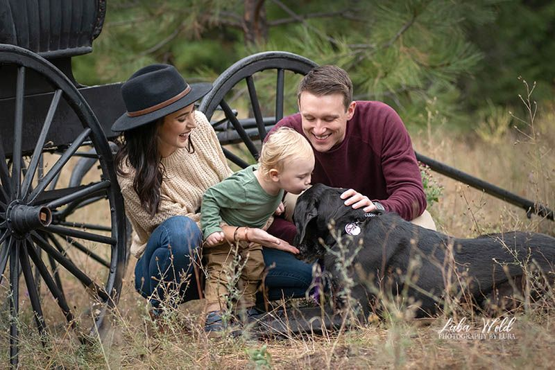 family of three playing by a wagon, little boy is kissing a dog, taken by photography by luba in Post Falls Idaho