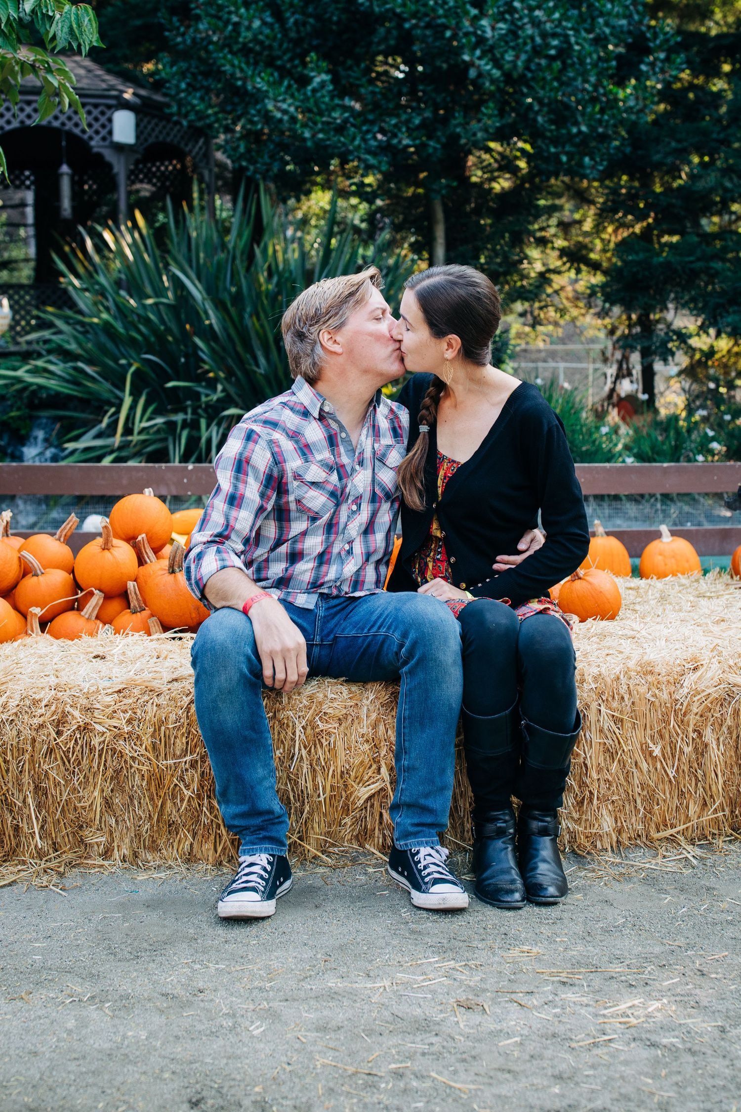 A camera-shy couple kisses at a pumpkin patch in northern California.