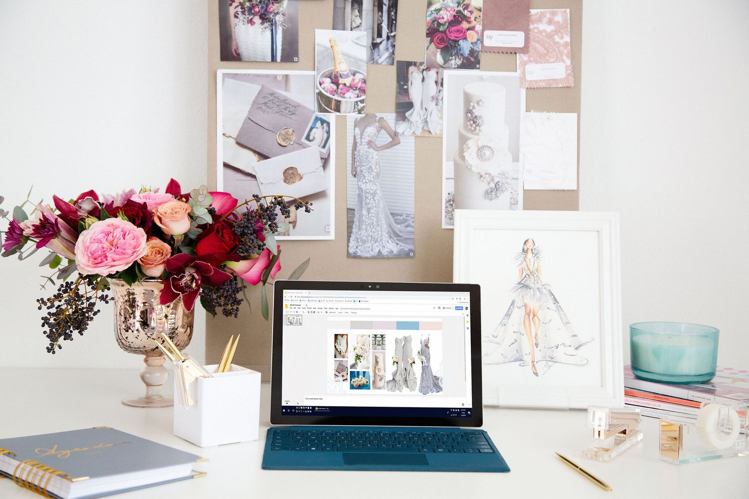 Feminine office setting. Desk with laptop and flowers.