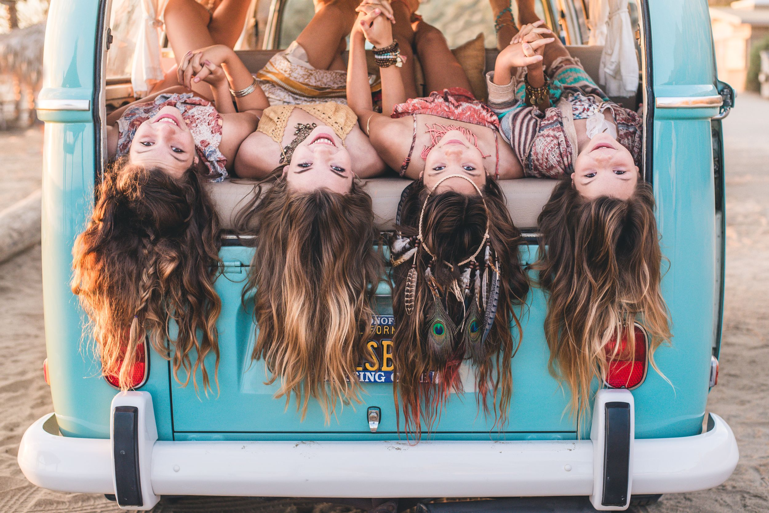 Teen girls in Volkswagen Bus  on the beach in Dana Point, CA