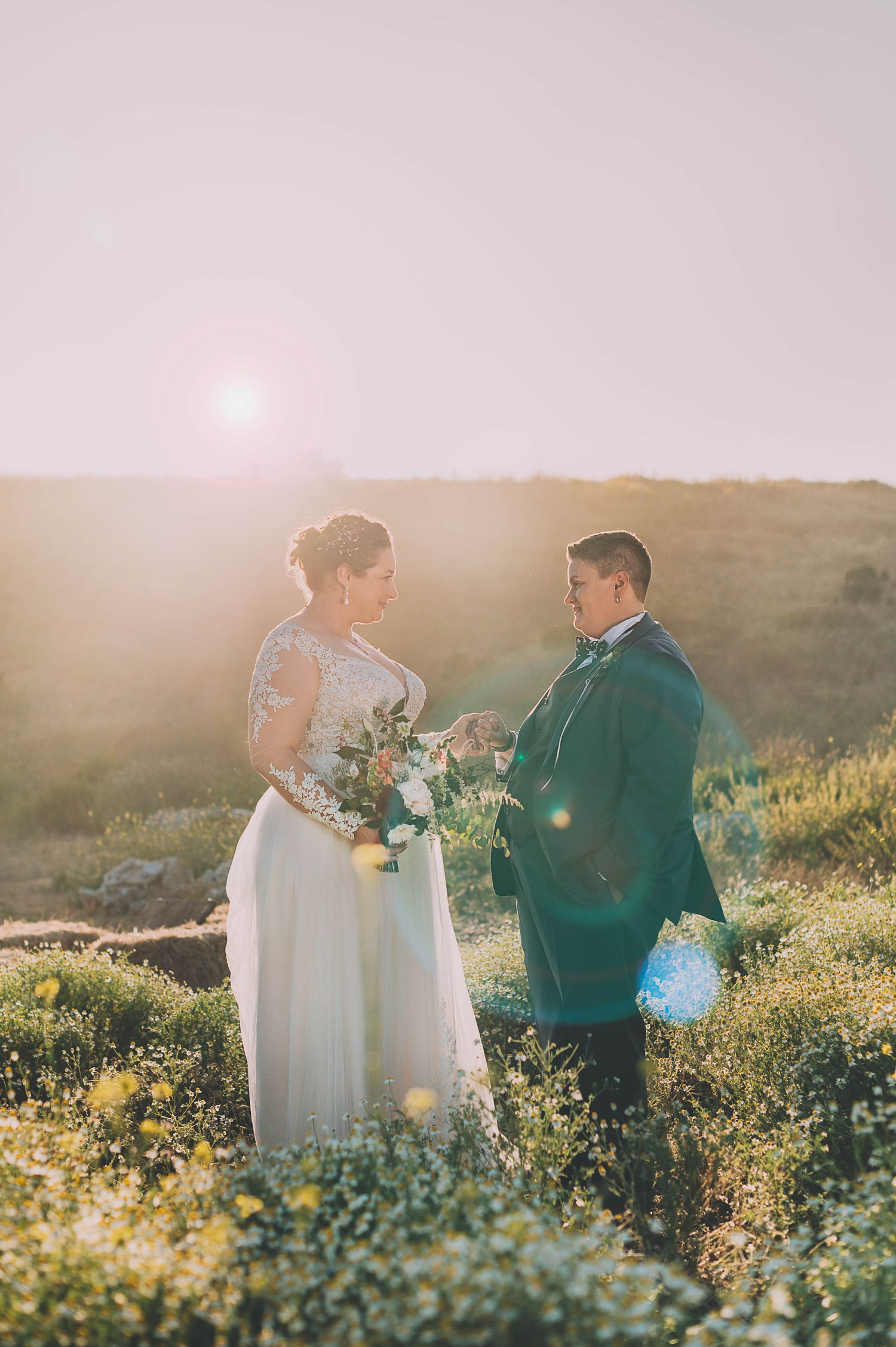 Lesbian couple wedding portrait at sunset with sun flare in Santa Cruz.