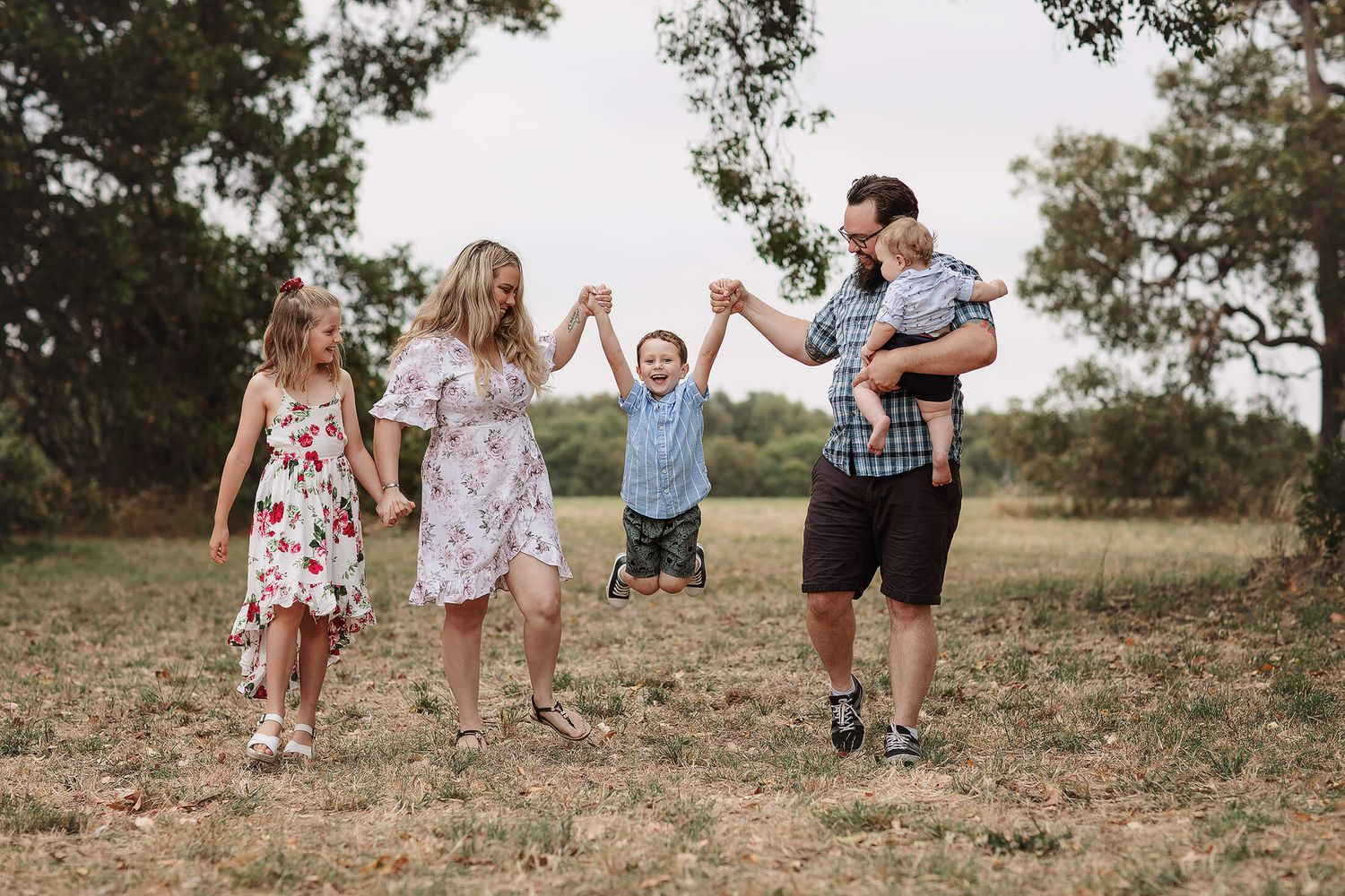 A family of 5 playing in a field at sunset for a family photo shoot in Perth, Western Australia