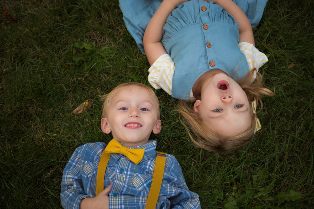 brother and sister laying in grass looking up at camera