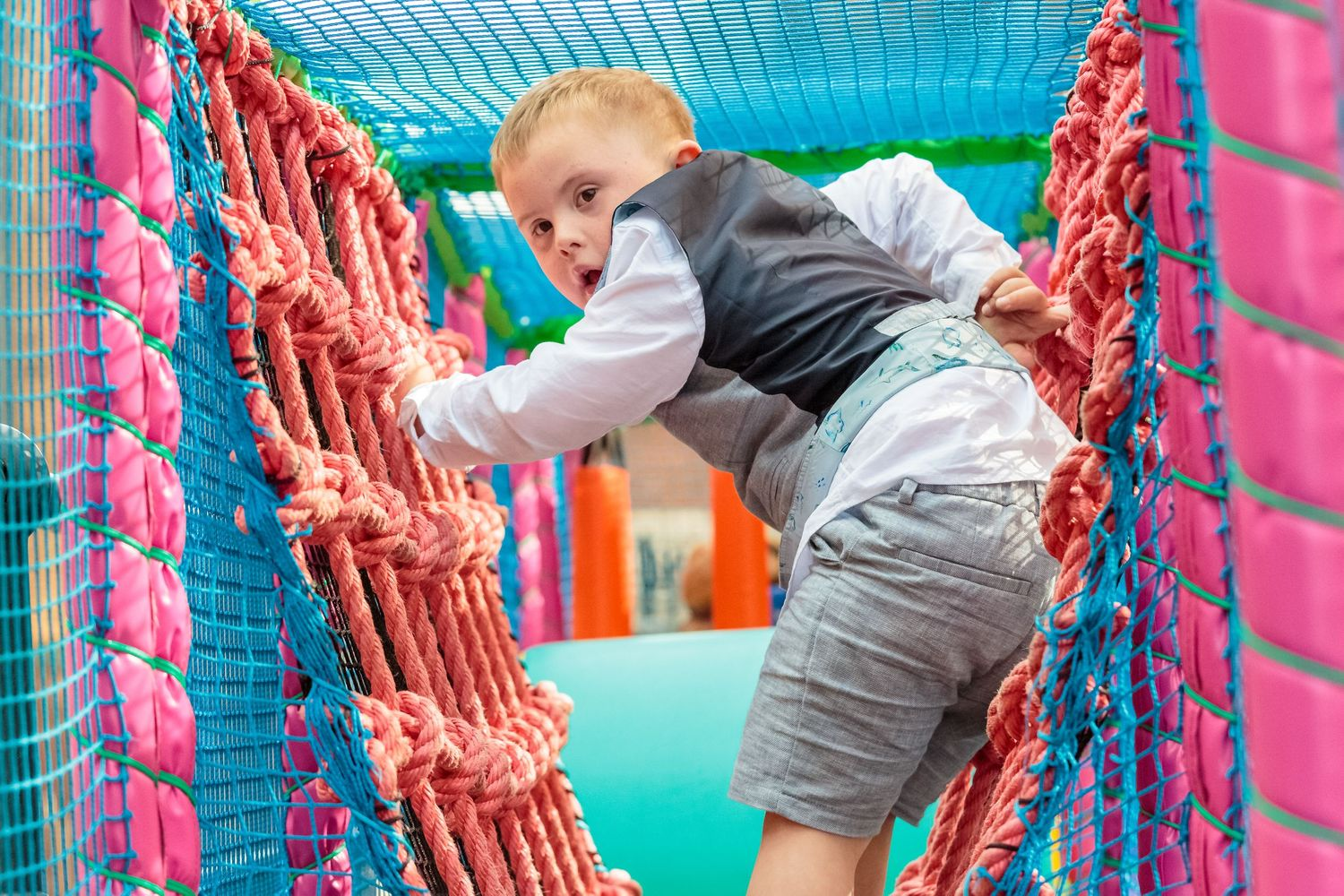young boy on a climbing net looks back at the camera