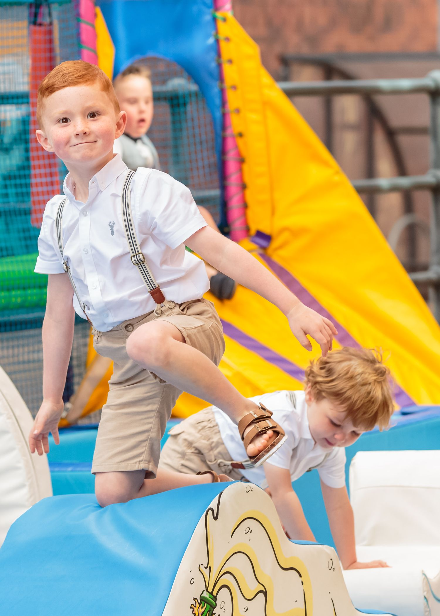 young boy smiling as he plays on a soft play area outside siren liverpool