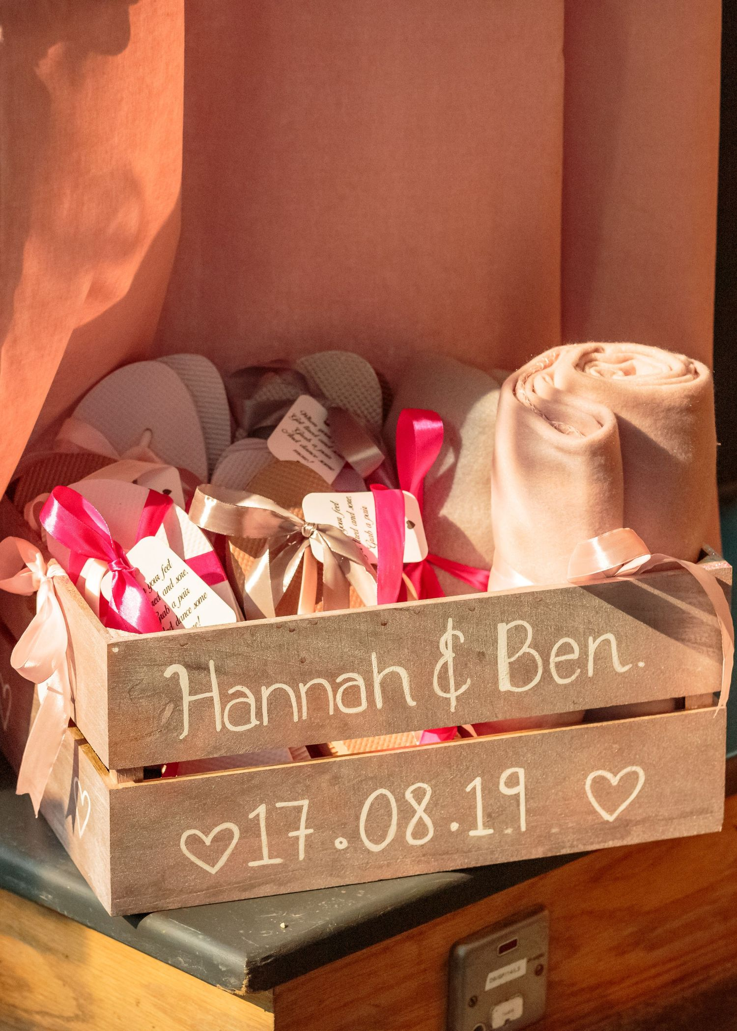 rustic crate of flip flops with the bride and grooms names and the wedding date on the side