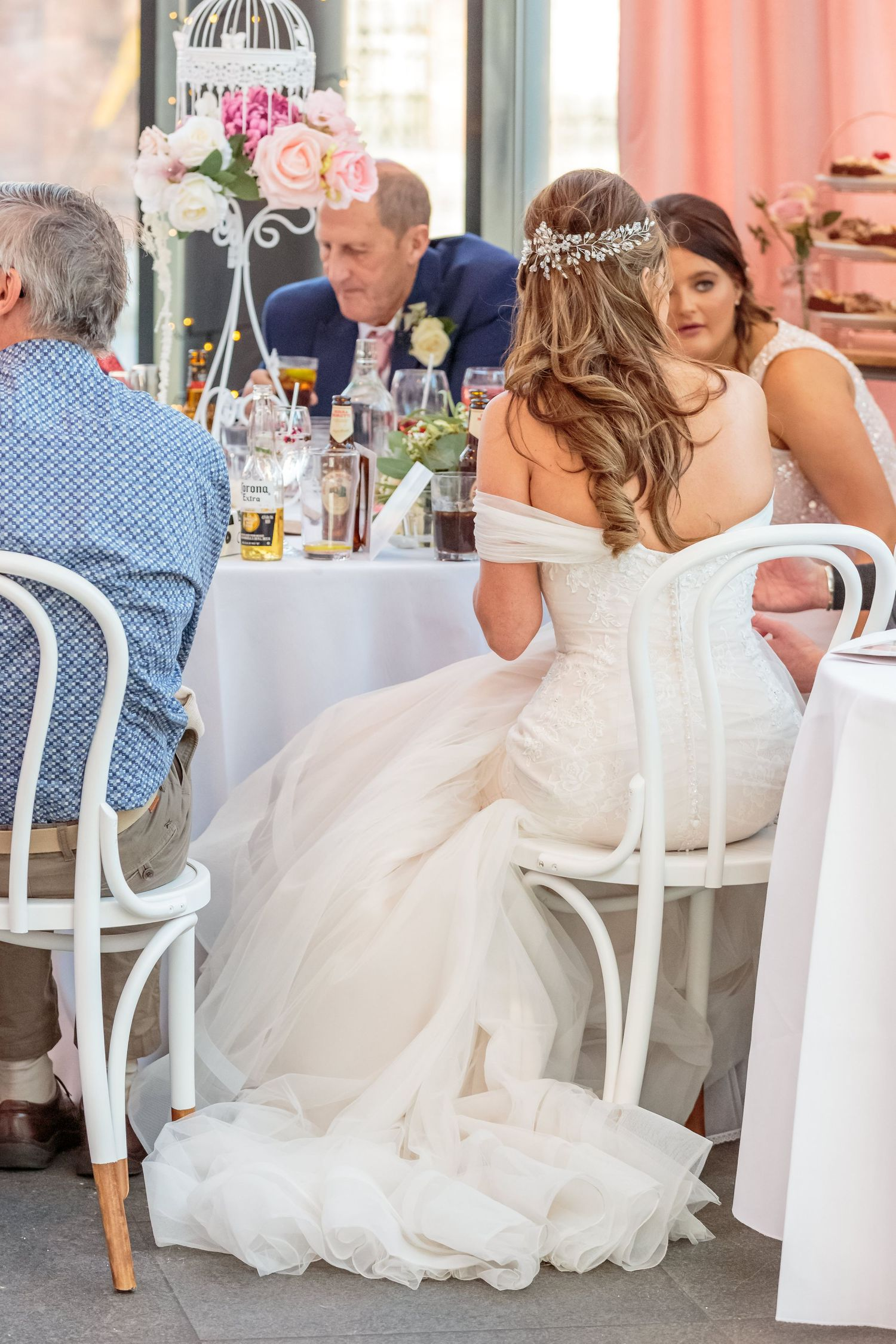 brides dress looks stunning from behind as she sits on an ornate metal chair in siren liverpool