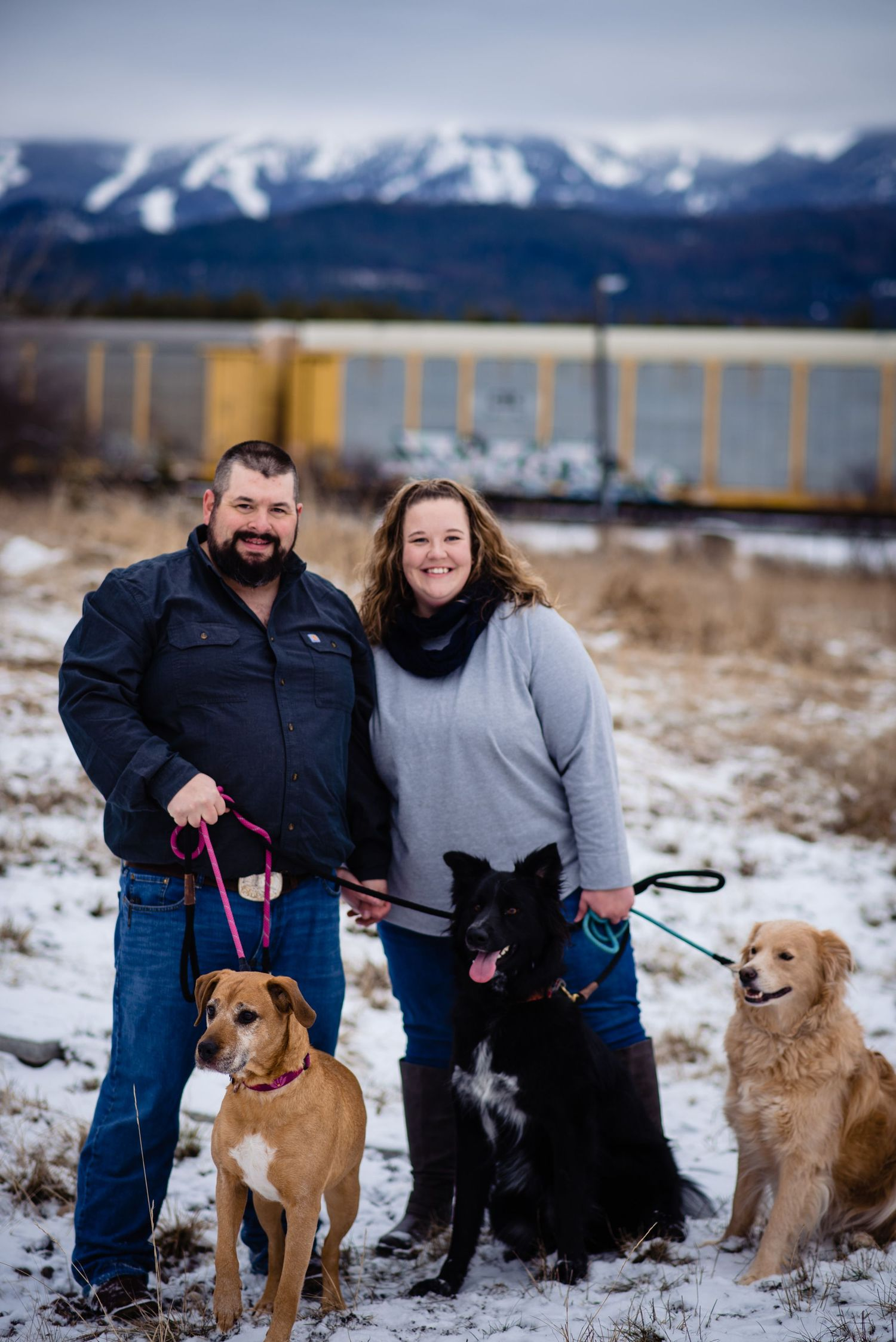 couple standing together for photo, three dogs on leashes in front of couple