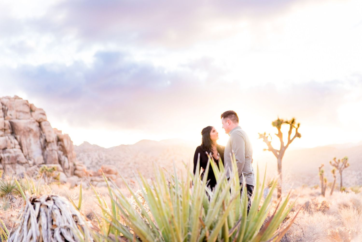 engaged couple look at each other while standing in front of rocks and trees under a sunset at Joshua Tree National Park