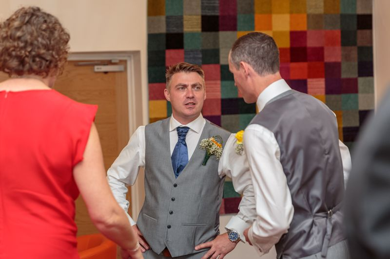 groom hands on hips chats with his best man at the oriel hotel