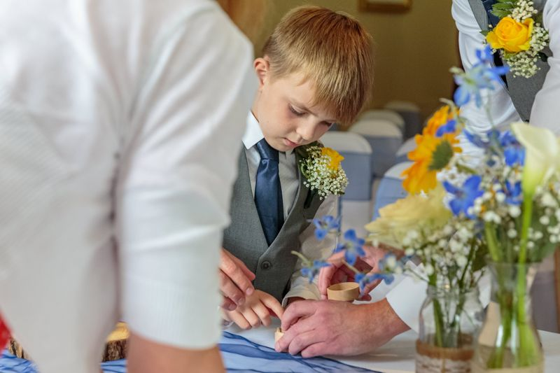 grooms young son checks the wedding rings in the box