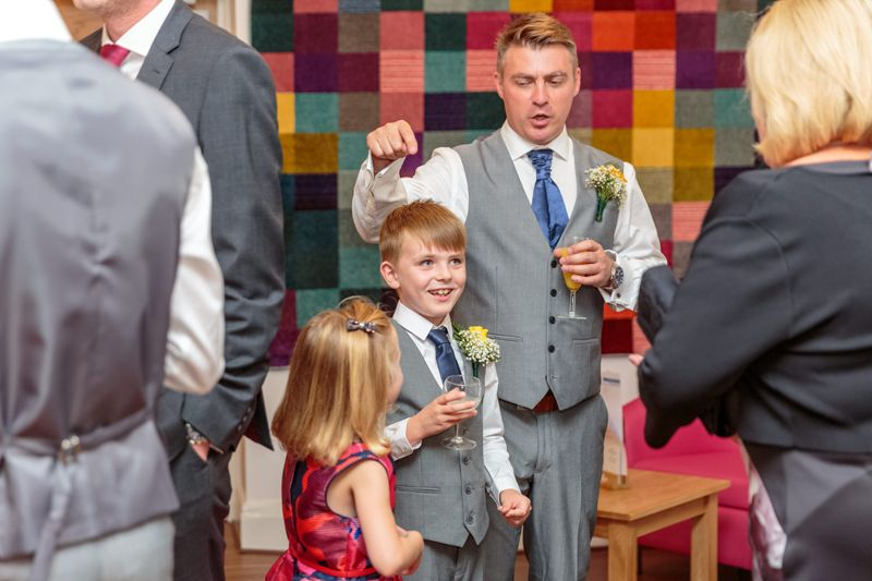 groom pointing at his sons head as he chats with wedding guests