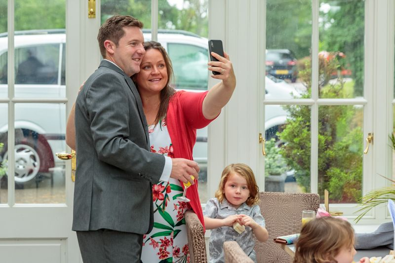 wedding guest couple take a selfie in the conservatory at the oriel hotel st.asaph