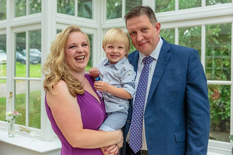couple pose for a photograph with their young son at claire and ben's wedding
