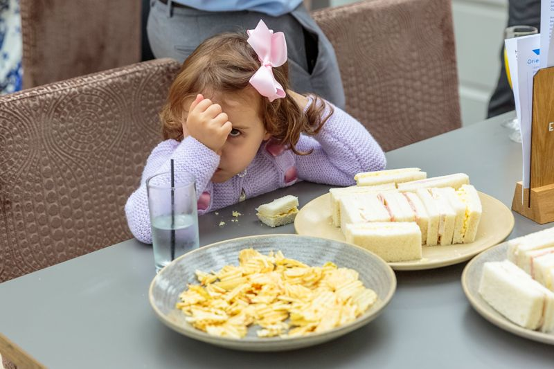 little girl hides her face behind her hand sitting at the table with a plate of crisps and sandwiches