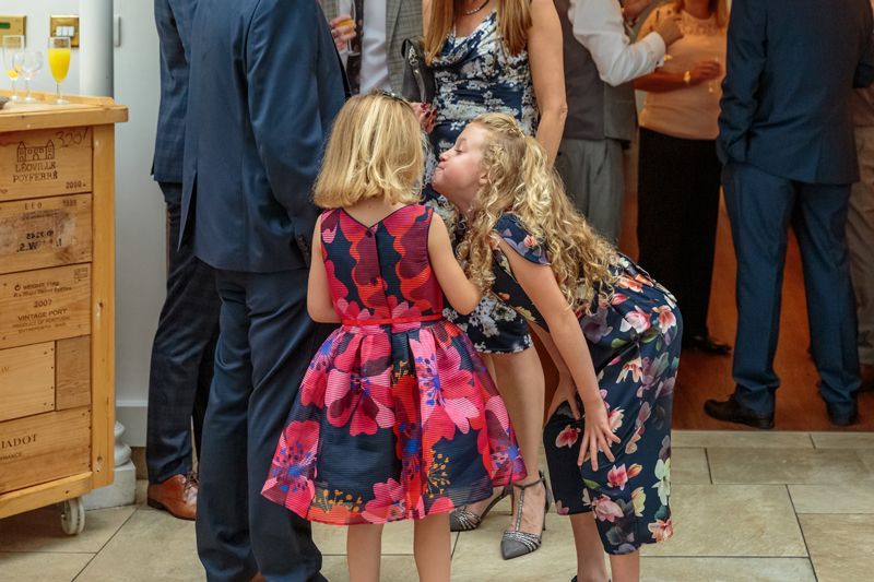 young girl puffs out her cheeks and pulls a face at her friend at ben and claires wedding