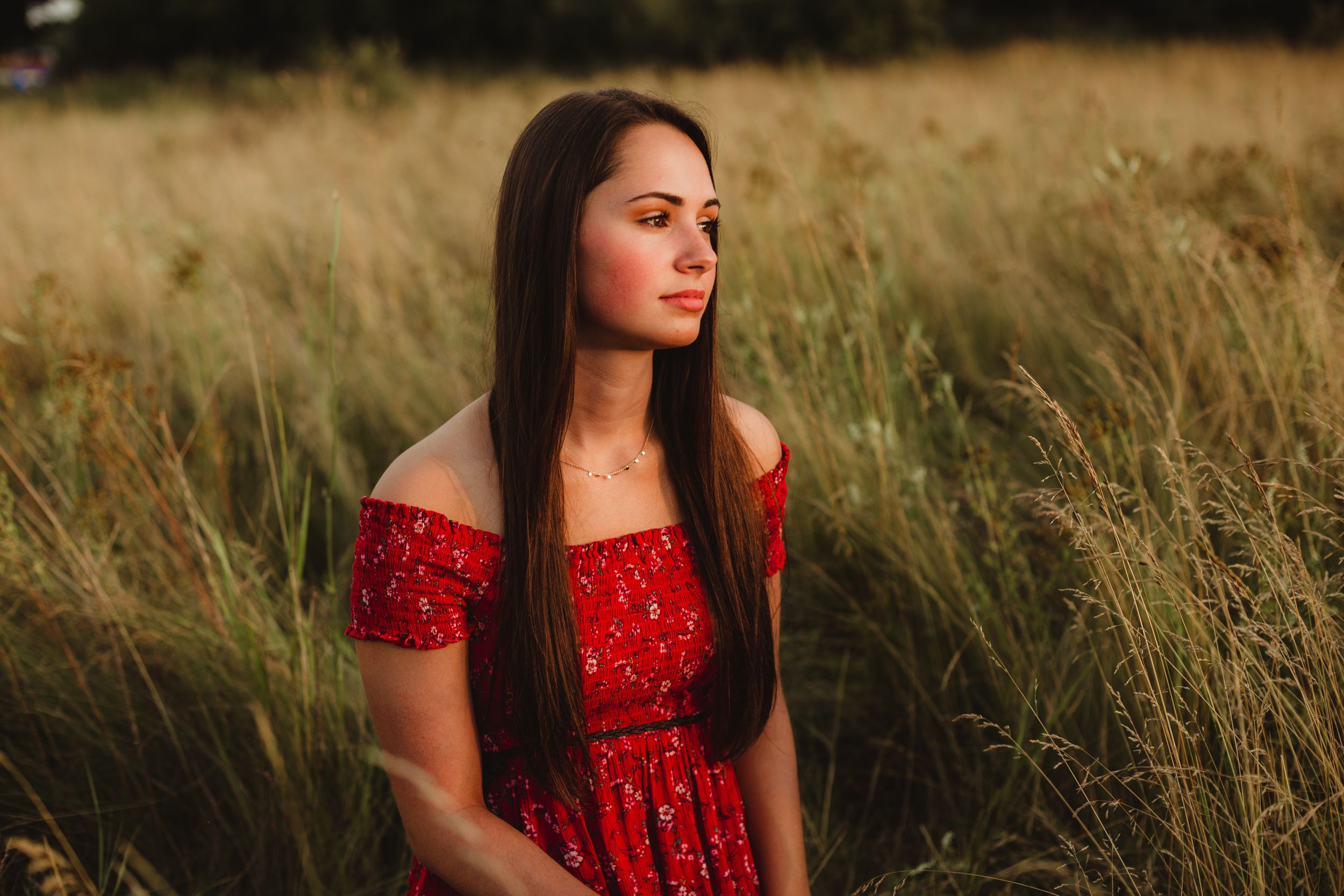 High school senior girl with long dark hair and a red dress sitting in an overgrown field facing the sunset.