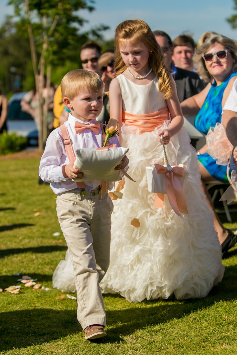 The ring bearer & flower girl walk down the aisle during a wedding ceremony at Cobblestone Golf Club in Blythewood, SC
