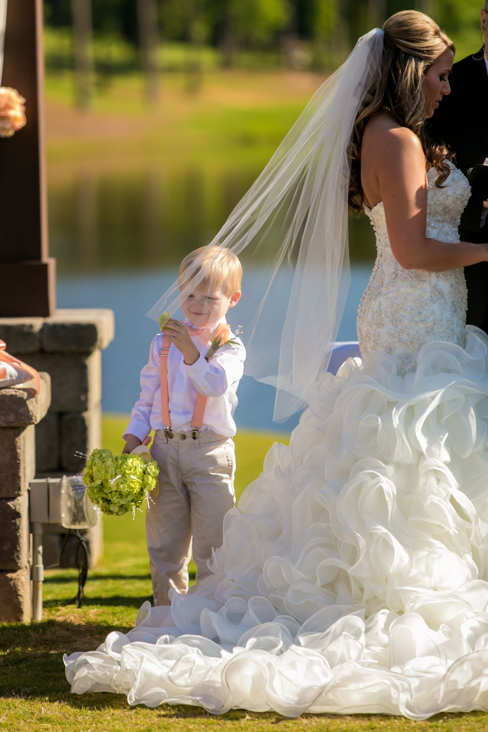 Ring bearer touches the bride's veil during a wedding ceremony at Cobblestone Golf Club in Blythewood, SC