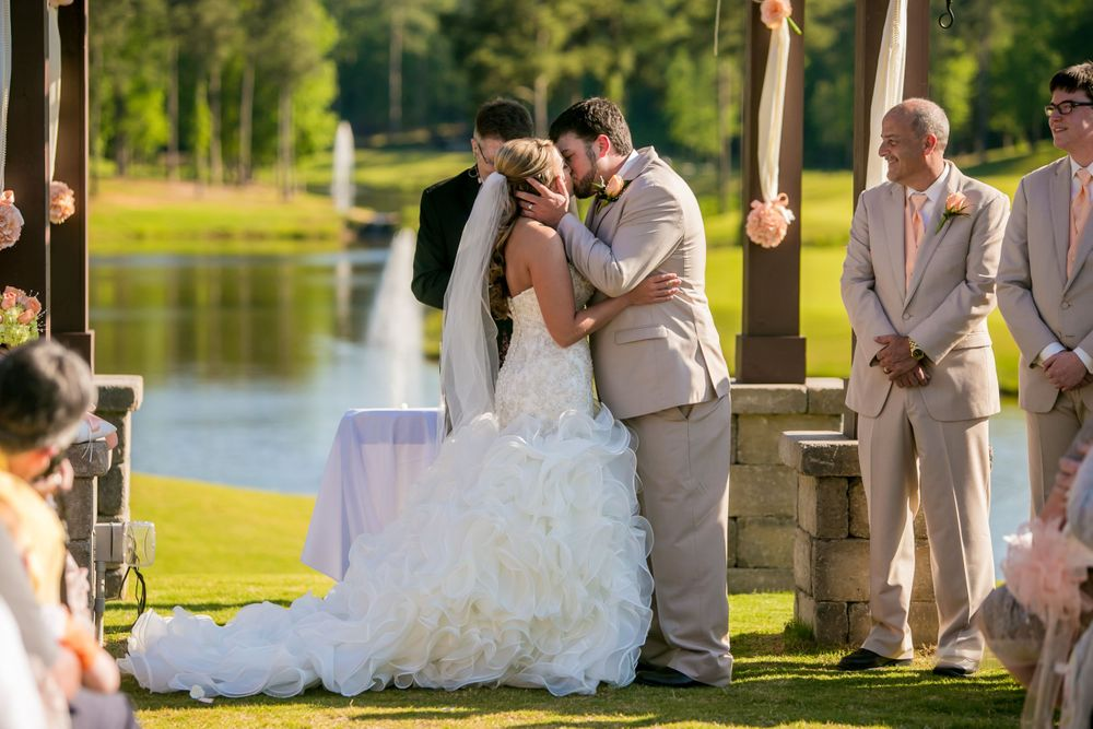 Bride Angela and groom Justin have their first kiss during a wedding ceremony at Cobblestone Golf Club in Blythewood, SC