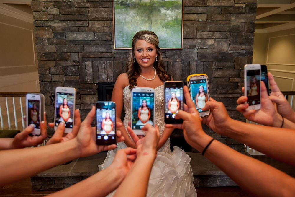 Angela's bridesmaids take her photo with their smart phones before a wedding at Cobblestone Golf Club in Blythewood, SC
