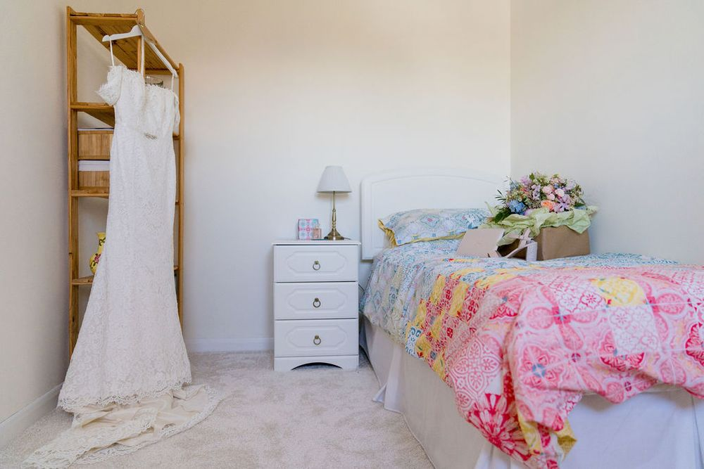 wedding dress hanging in bedroom