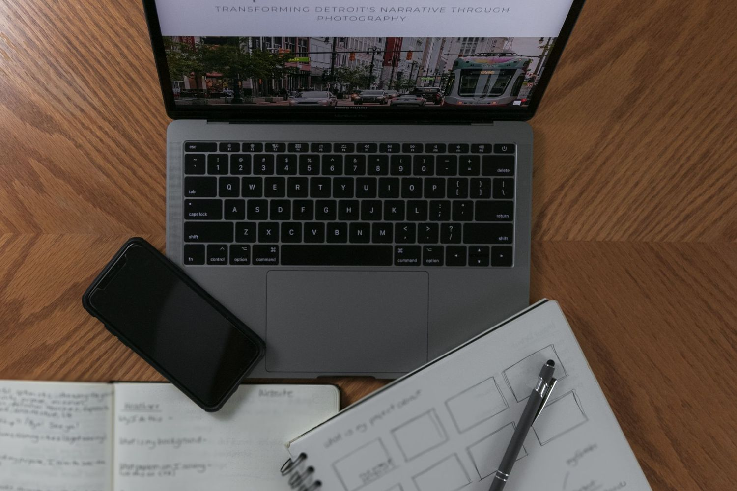 Flat lay image of open laptop with notebook and cell phone