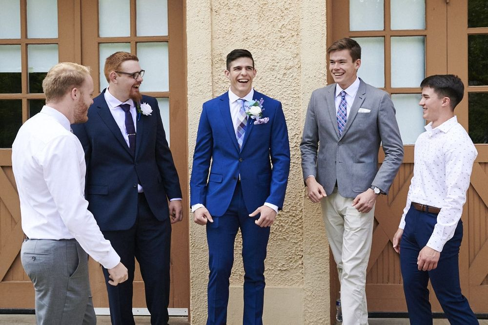 groom and groomsmen laughing in front of garage at Lord Mansion in Olympia, WA