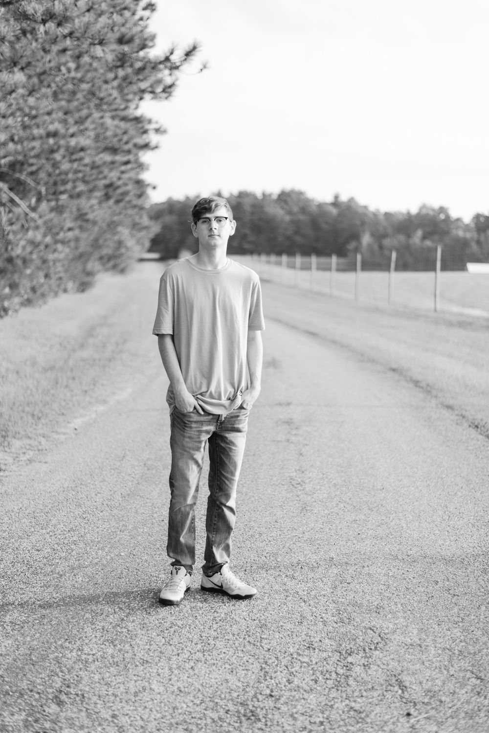 Senior boy standing on road black and white
