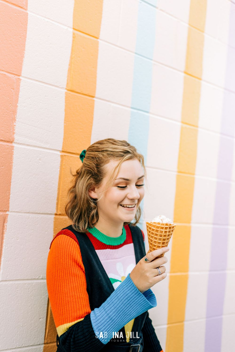 Young woman during senior portraits in Jeni's Ice Cream Shop in NODA
