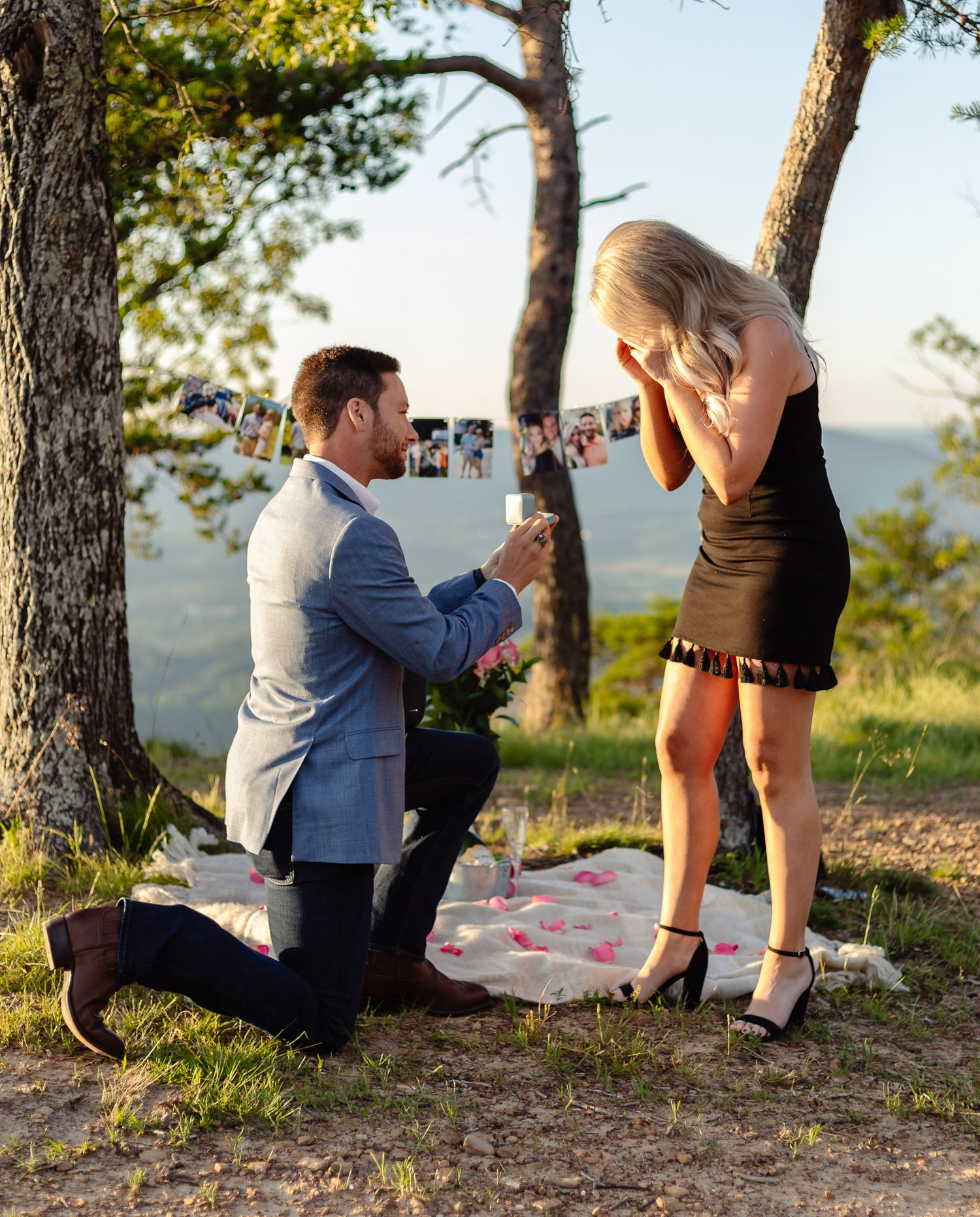 A man wearing a blue suit proposes to a woman wearing a black dress at sunset.