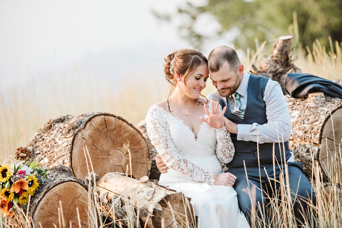 Bride and groom admire bridal ring while sitting on logs