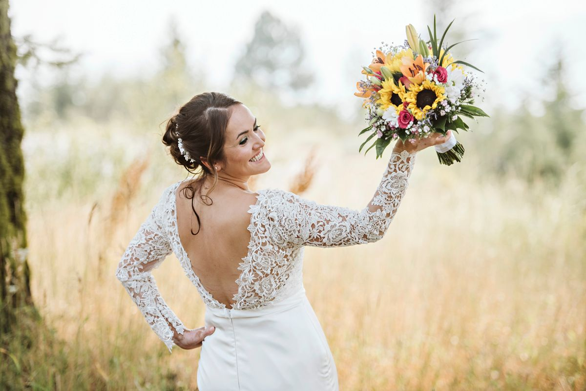 Bride shows off the back of her gown and her bouquet