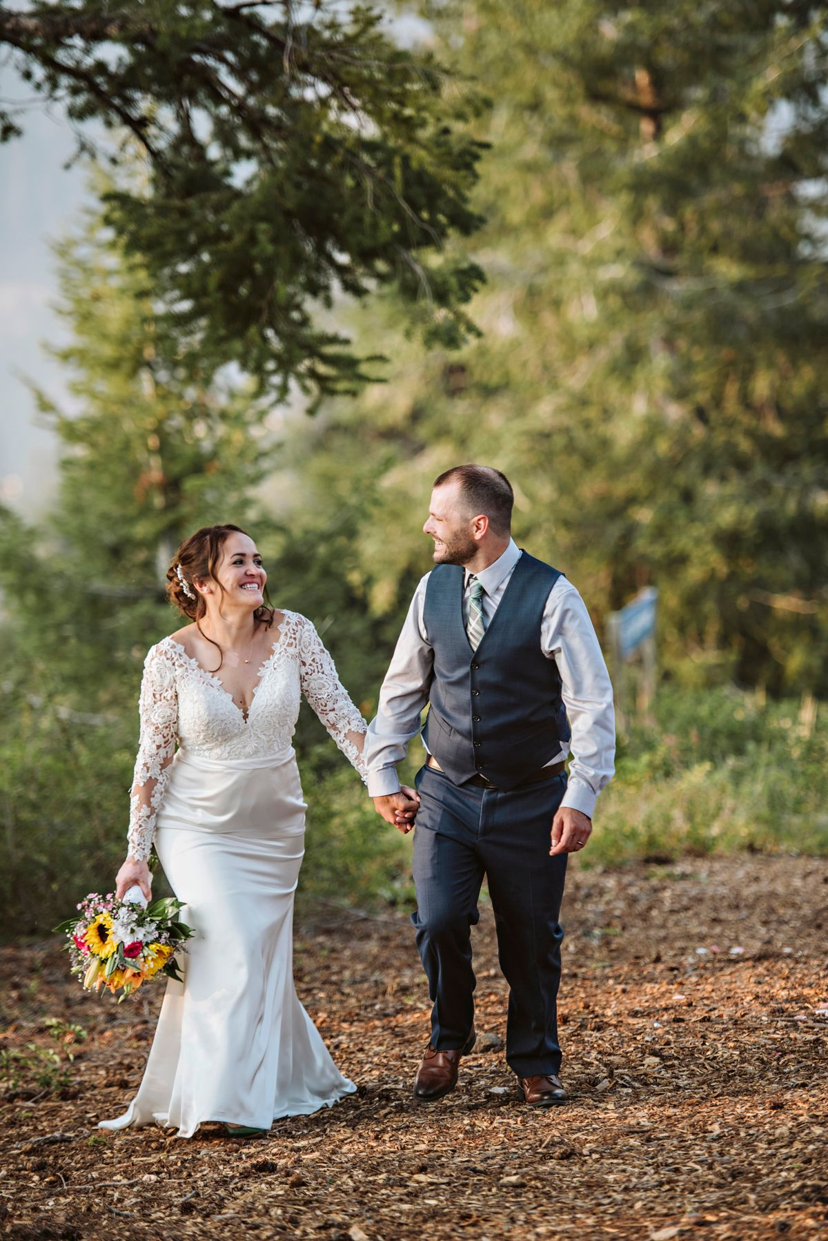 Bride and groom walk in the pines