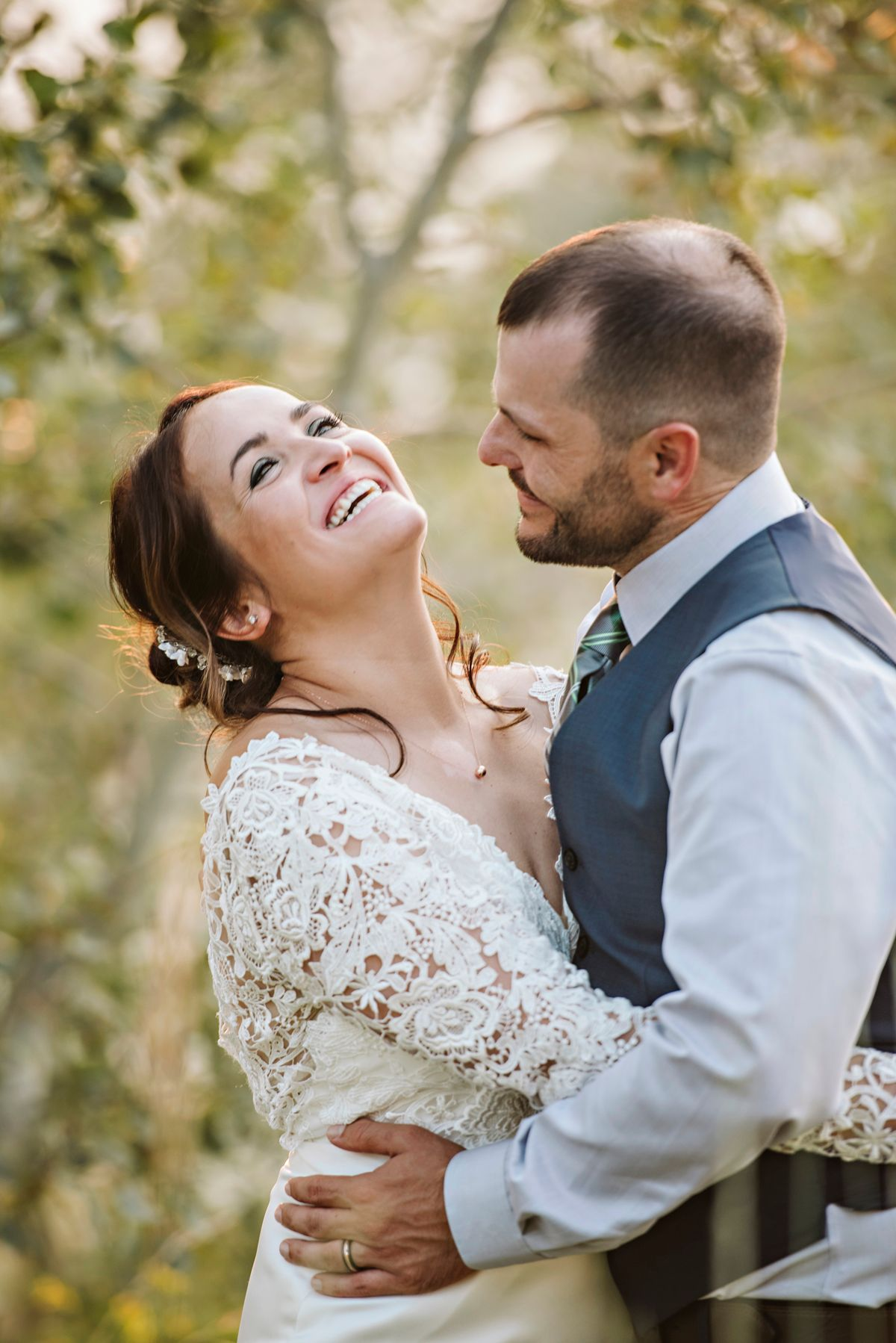 Bride laughs as groom adores her