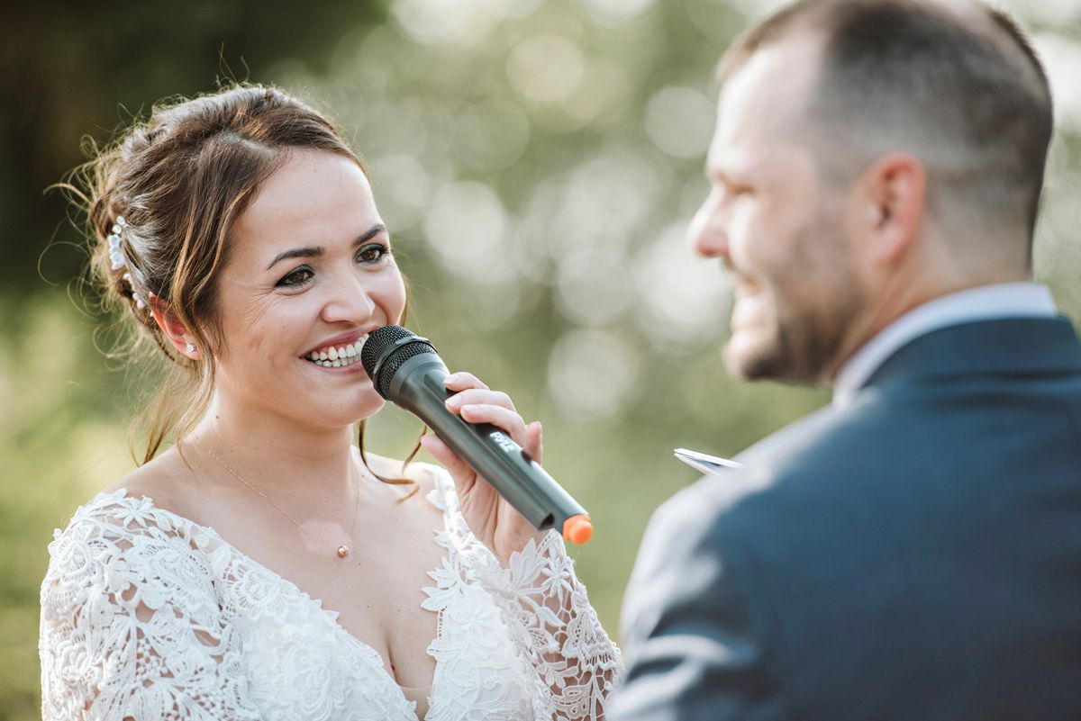 Bride says vows in microphone as groom smiles