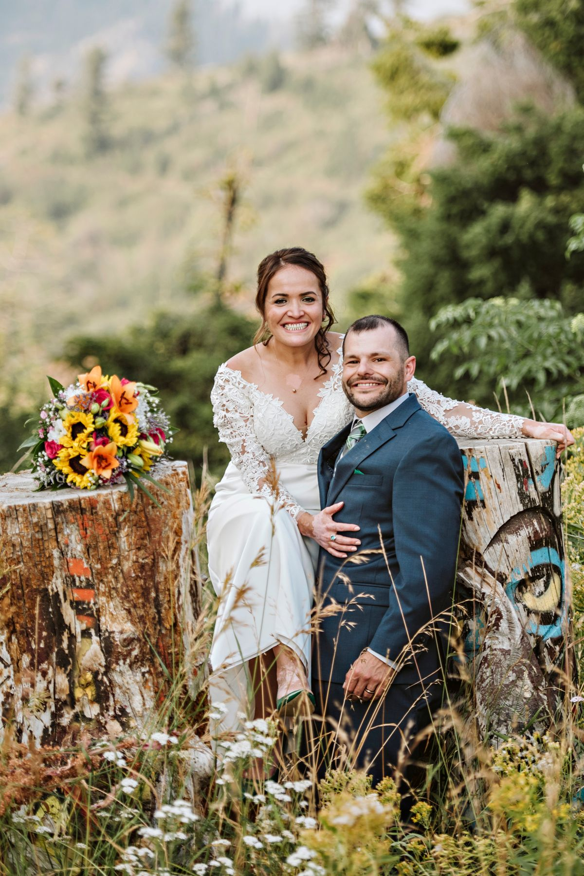 Couple pose on logs after wedding on Bogus Basin