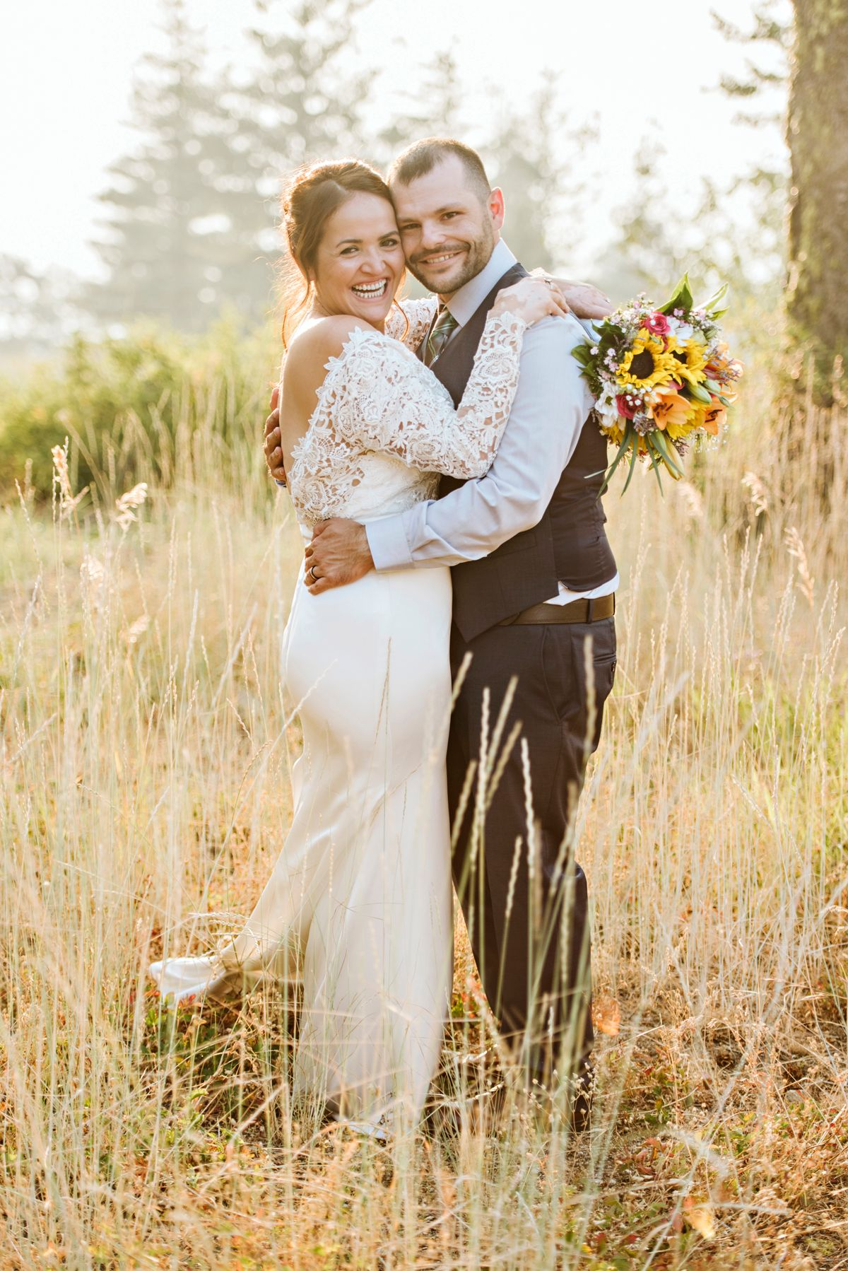 Bride and groom pose in the tall grass after wedding